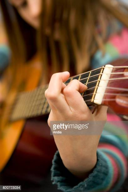 Young girl teenager learning how to play the guitar Hand playing chords closeup