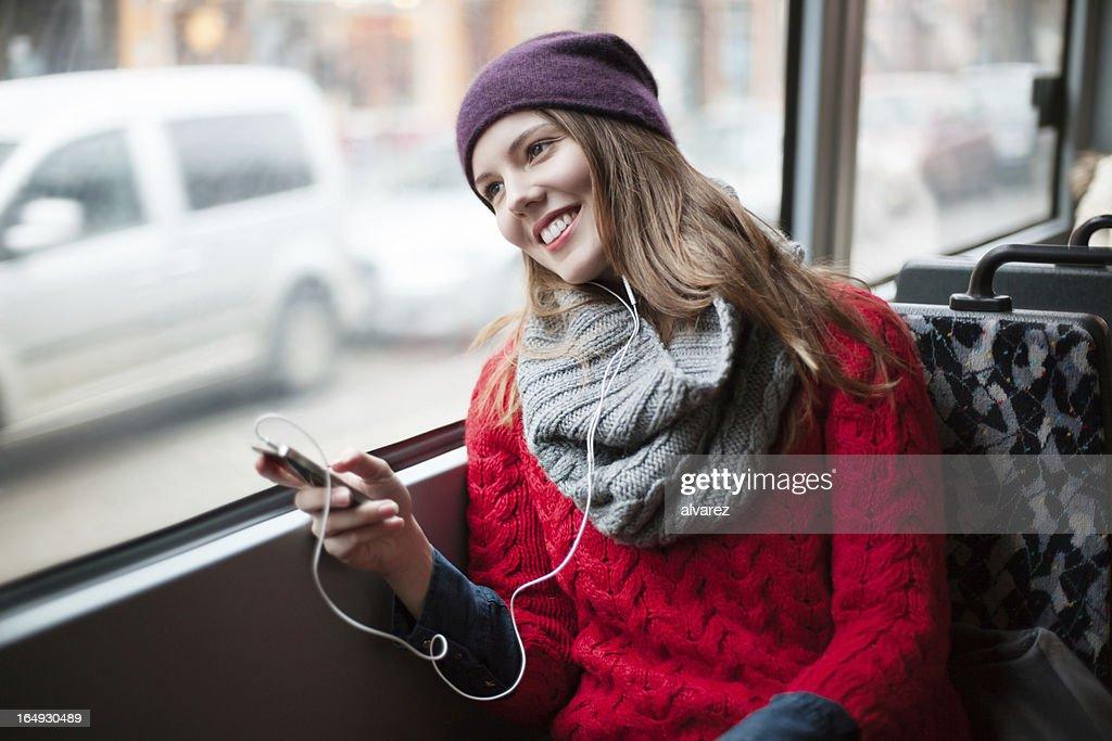 若い女の子の彼女のリラクゼーションに電話での公共交通機関 : ストックフォト