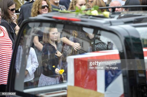 CROP A young girl throws a single yellow rose on to the second hearse as three pass through the town of Wootton Bassett during the repatriation of...