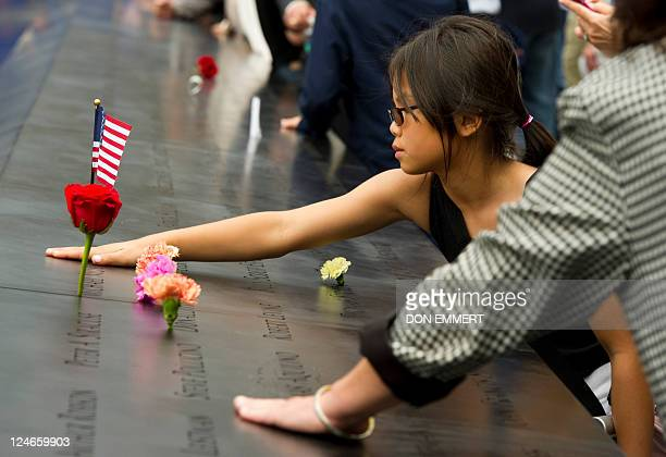 A young girl touches a name on the 9/11 memorial South Tower pool of the World Trade Center September 11 2011 in New York as the US marks 10 years...