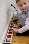 A young girl touching an electric outlet