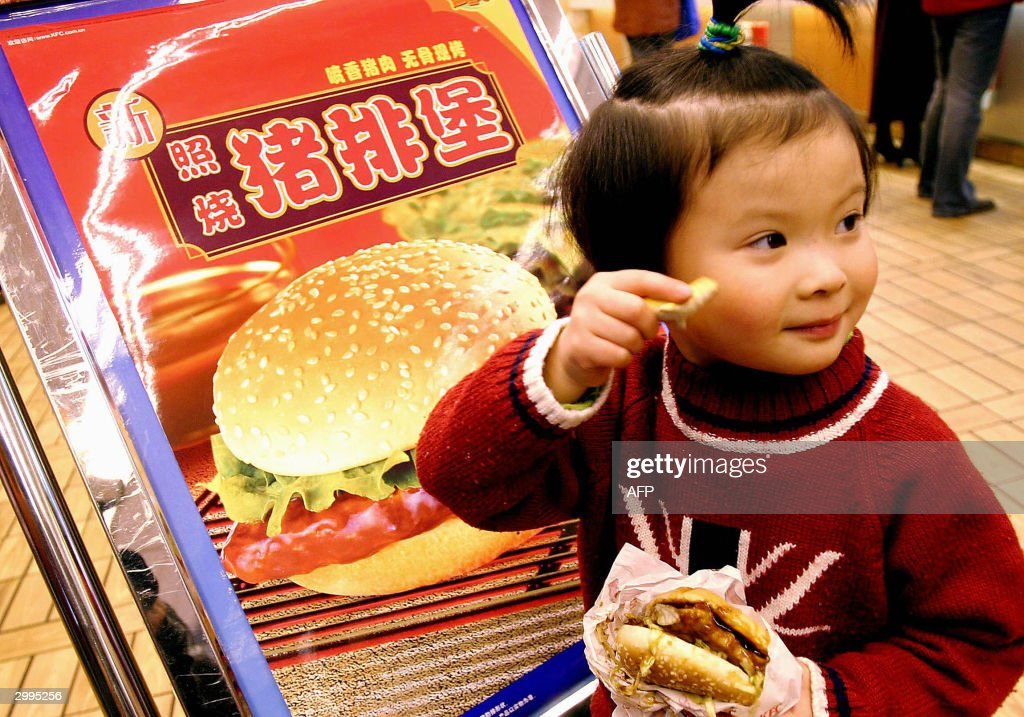 A young girl tries out the new US fastfood giant Kentucky Fried Chicken's roast pork burgers at their Beijing outlets 19 February 2004 Chinese spent...