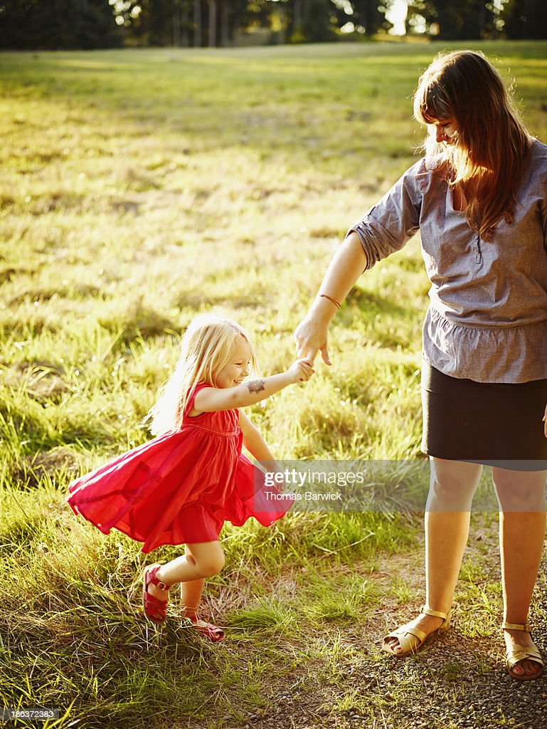 Young girl twirling holding mothers hand : Stock Photo
