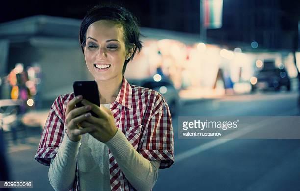 Junges Mädchen Tippen Nachrichten auf der Stadt-Straße