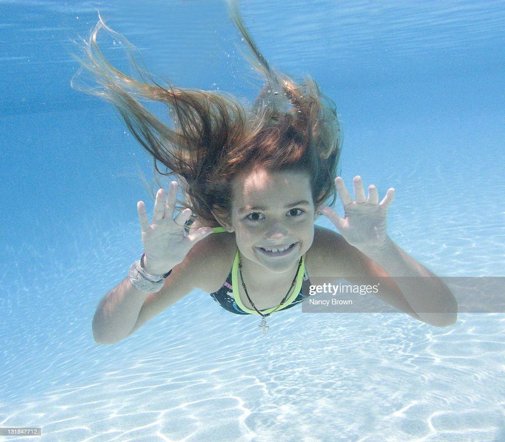 Young girl underwater swimming to camera. : Stock Photo