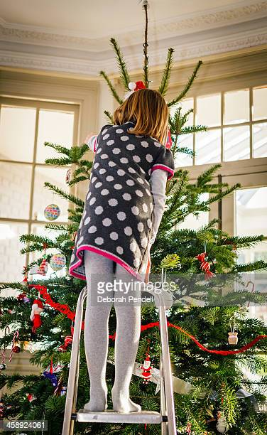 Young girl up a ladder decorating Christmas tree