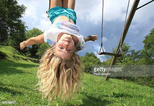 A young girl upside down on playground