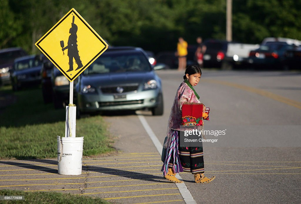 A young girl uses a designated crosswalk on her way to a tribal dance passing a crossing sign depicting a Native American Her costume is made of...