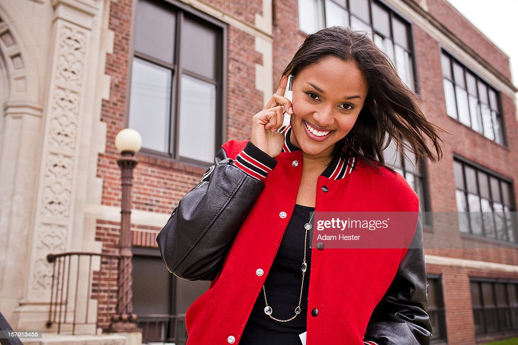 A young girl using a cell phone outside. : Stock Photo