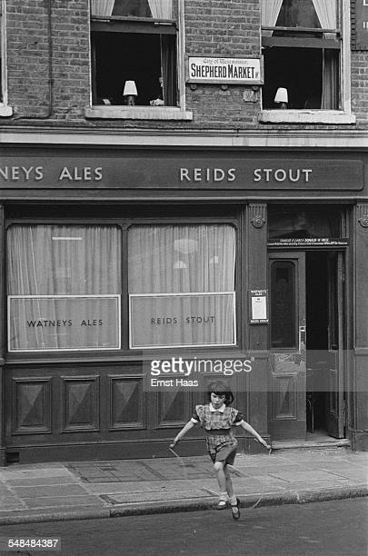 A young girl using a skipping rope outside a public house in Shepherd Market Mayfair London circa 1953