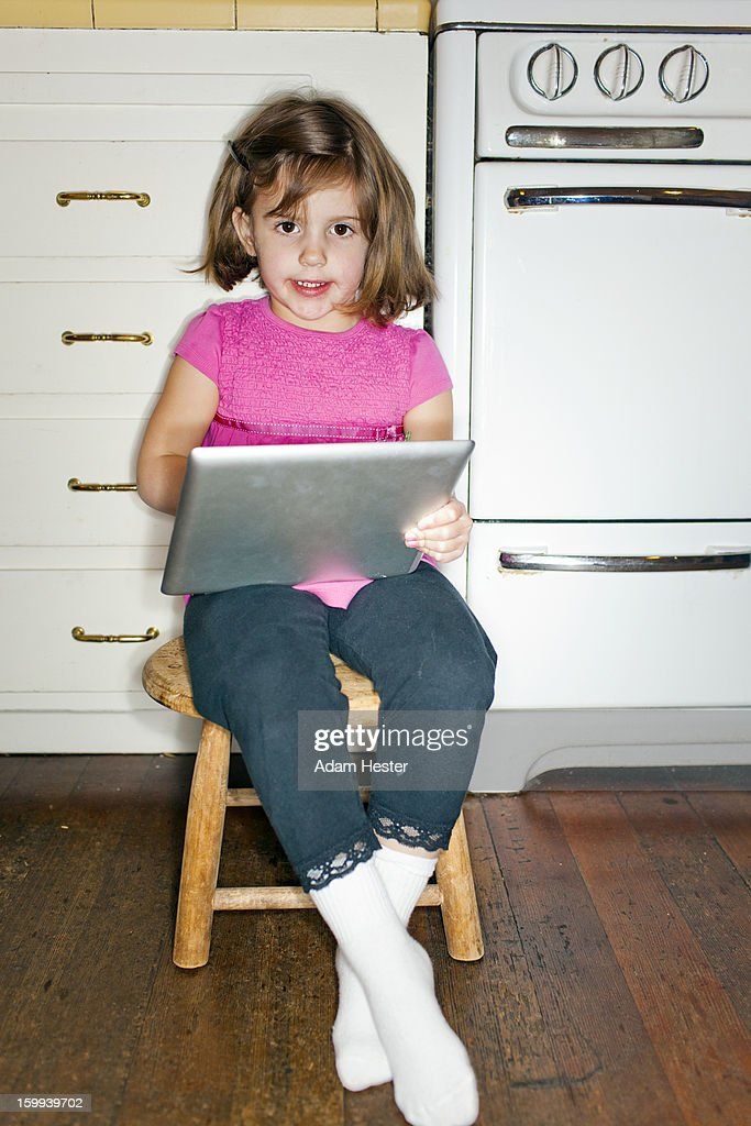 A young girl using a tablet device inside a home. : Stock Photo