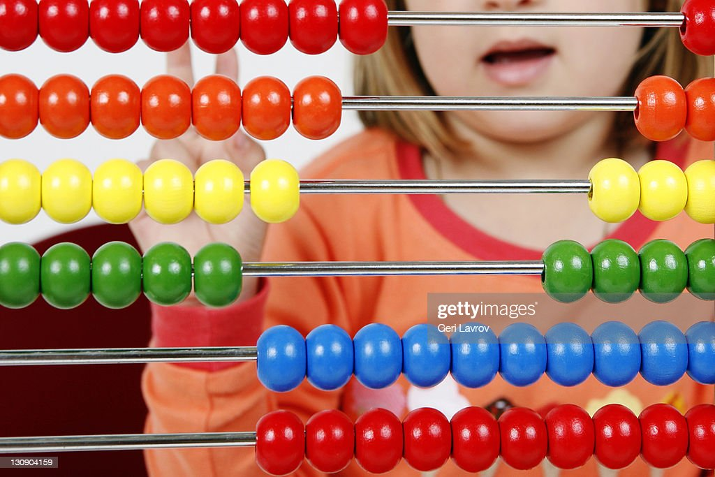 Young girl using an abacus : Stock Photo