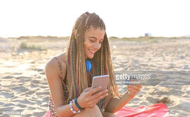 Chica joven usando tarjeta de crédito en la playa