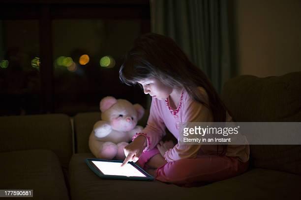 Young girl using digital tablet at night