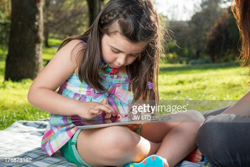 young girl using digital tablet in the park : Stock Photo