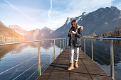 Traunsee lake in Austria , in background are Traunstein mountains , 16 year old girl using phone on a dock in lake , posting photo on internet