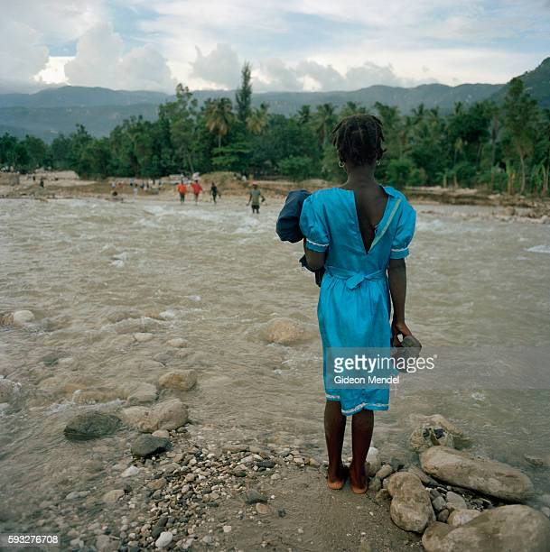 A young girl waits for a porter to help her cross the River Perdo in Savane Dubois in southeast Haiti Hurricane Gustav destroyed the bridge here so...