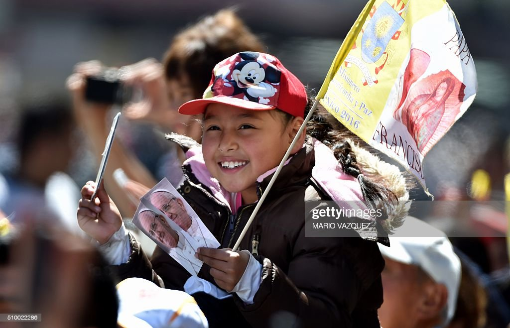 A young girl waits for the passage of Pope Francis on his way to the Nuncianture, in Mexico City on February 13, 2016. Francis became the first pope to enter Mexico's National Palace to meet President Enrique Pena Nieto, as he starts a cross-country tour that will highlight the country's violence and migration troubles. AFP PHOTO. AFP PHOTO/MARIO VAZQUEZ / AFP / MARIO VAZQUEZ