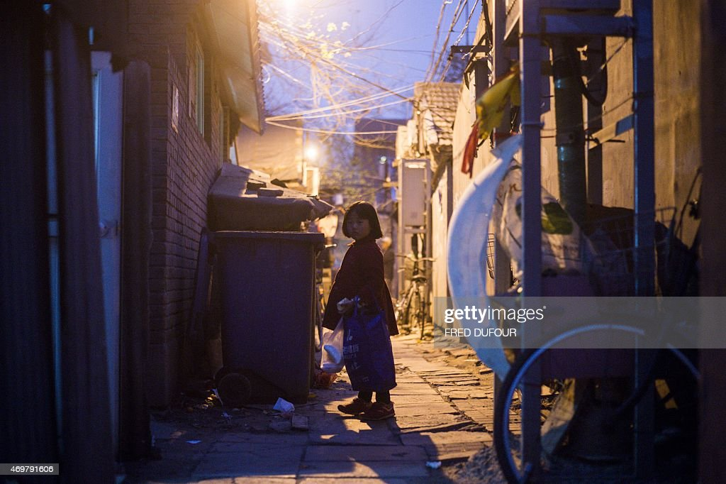 A young girl waits in a 'hutong' or alleyway during a sandstorm in Beijing on April 15 2015 Beijing's meteorological observatory issued a yellow...