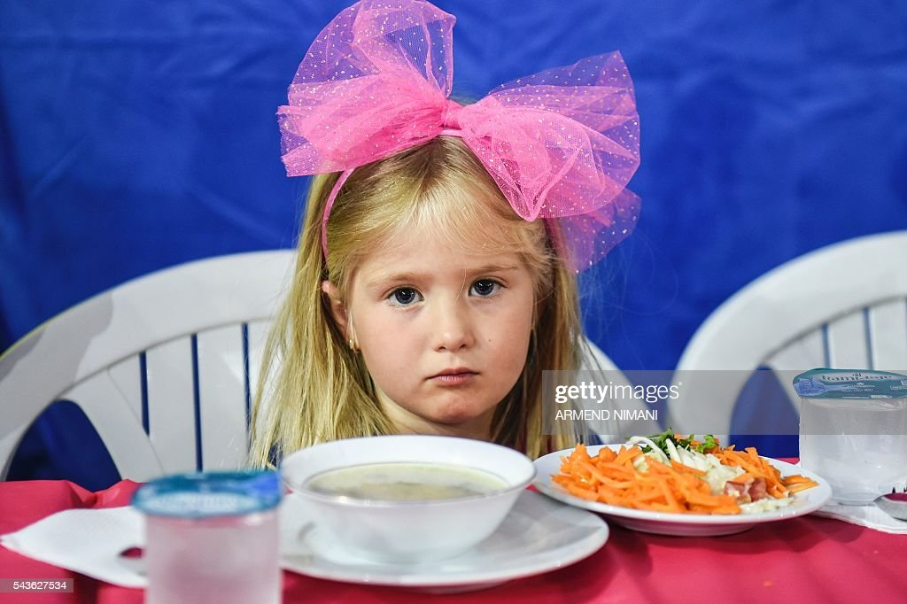 A young girl waits to break the fast with a dinner distributed for free during the Muslim fasting month of Ramadan on June 29, 2016 in Pristina. Muslims fasting in the month of Ramadan must abstain from food, drink and sex from down to dusk, when they break the fast with meal known as iftar. / AFP / ARMEND