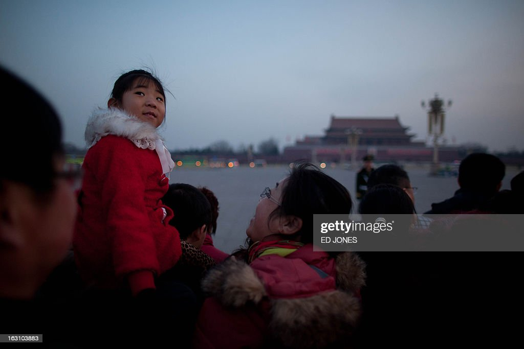 A young girl waits to watch the daily flag-raising ceremony on Tiananmen Square in Beijing early on March 5, 2013. Thousands of delegates from across China meet this week to seal a power transfer to new leaders whose first months running the Communist Party have pumped up expectations with a deluge of propaganda. AFP PHOTO / Ed Jones
