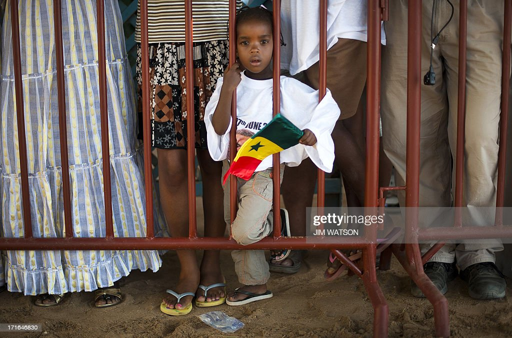 A young girl waits with others behind a barricade as the US president tours Goree Island off the coast of Dakar in Senegal, June 27, 2013. US President Barack Obama and his family toured the the House of Slaves at the site where African slaves were held before going through the door and being shipped off the continent as slaves.
