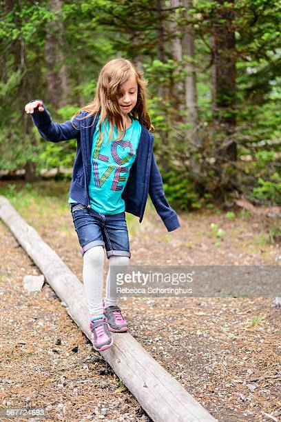 Young girl walking across log in forest