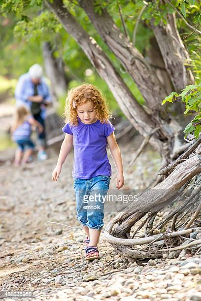 Young Girl Walking Along River Bank in Summer