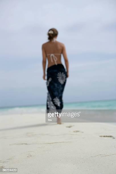 Young girl walking at the beach, footprints at sand, rear view