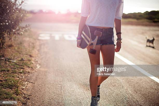 Young girl walking down with her longboard