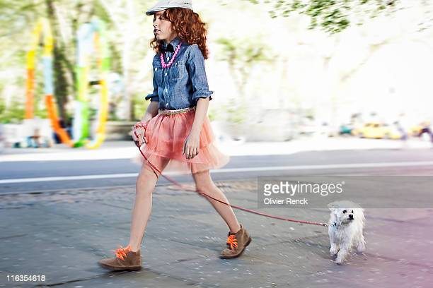 A young girl walking her dog near Central Park in New York, New York.