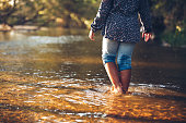 Shoulders down view of a young girl walking away in a shallow creek. End of summer, fall color and feel.