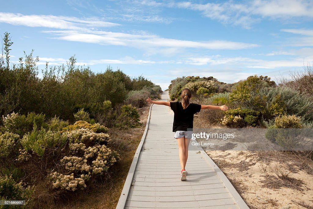 Young girl walking on a footpath with arms raised