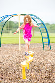 Front view of a young girl walking on a curved yellow balance beam on the playground at a park. This park also has a splash park area with fountains, so the girl is wearing a pink and orange rash guar
