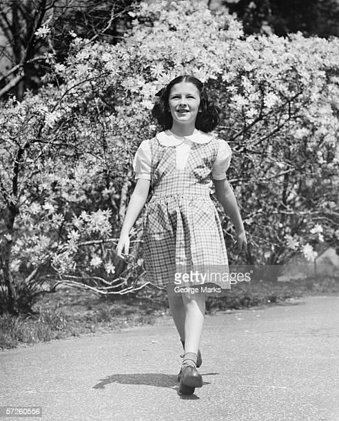 Young girl (8-9) walking on garden path, (B&W)
