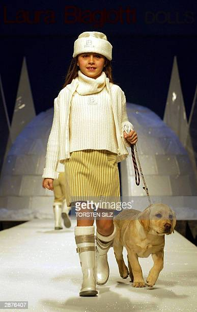 A young girl walks a dog as she presents the 2004/2005 fallwinter creations by Italian designer Laura Biagotti 17 January 2004 in Florence during the...
