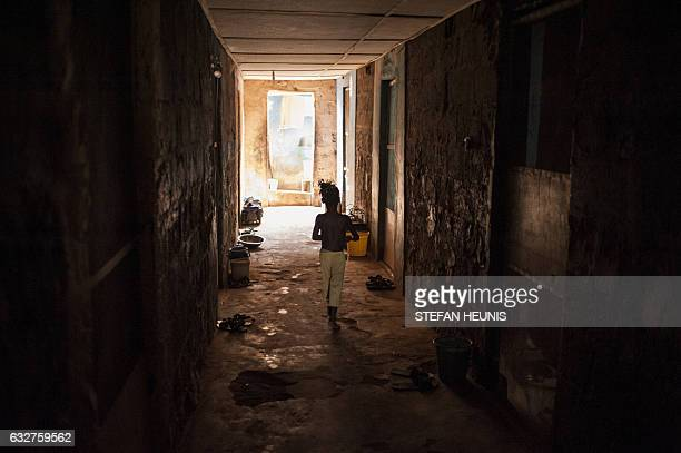 A young girl walks down a hallway in a shared accommodation house where families rent rooms on January 6 2017 in Lagos Nearly two years after taking...