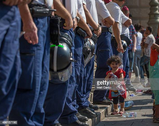 A young girl walks in front of Hungarian police officers guarding the main entrance as migrants protest outside Keleti station in central Budapest...