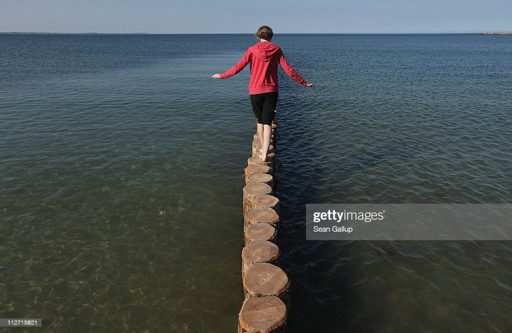 A young girl walks out onto a wooden wave break on a sunny day at a beach on the Baltic Sea on Ruegen Island on April 20, 2011 at Glowe, Germany. Most of Germany basked in spring sunshine today with temperatures reaching 23 degrees Celsius ahead of Easter Weekend.