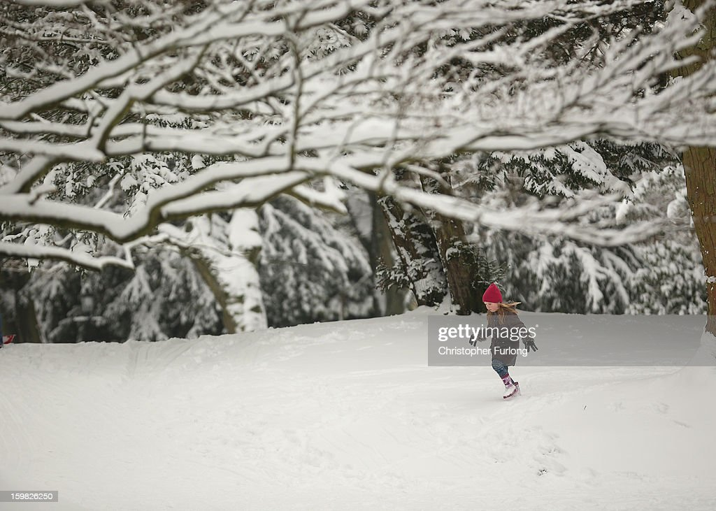 A young girl walks through the snow in The Pavilion Gardens on January 21, 2013 in Buxton, United Kingdom. The Met Office has issued a red weather warning for parts of the Uk and advising against all non-essential travel as up to 30cm of snow is expected to fall in some areas today. The adverse weather has closed nearly 5,000 schools and caused many airports to cancel flights.