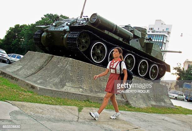 A young girl walks to school on in Cuba 03 September 2001 Una escolar pasa frente a un tanque de guerra expuesto en un museo local el 03 de setiembre...
