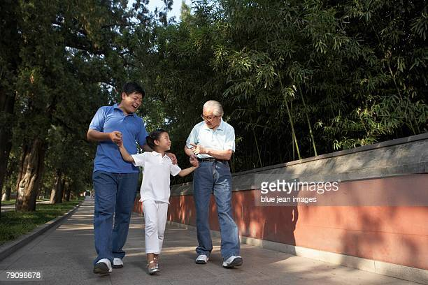 A young girl walks with her father and grandfather.