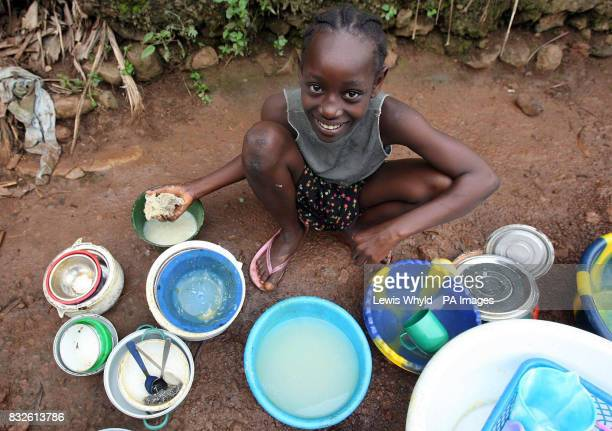 A young girl washes dishes by a river in Freetown Sierra Leone