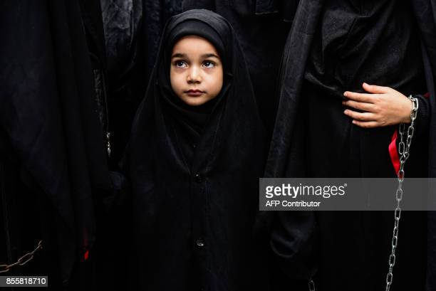 A young girl watches a reenactment with Turkish Shiite women of the Battle of Karbala ahead of the Shiite religious holiday of Ashura on September 30...