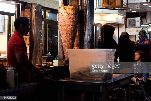 A young girl watches a street vendor making shwarma sandwiches March 18 2013 in Baghdad Iraq Ten years after the regime of Saddam Hussein was toppled...