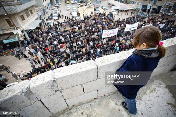 A young girl watches an antiAssad protest in the town of Binnish on April 9 2012 in Binnish Syria Conitnuing violence in northern Syria between...