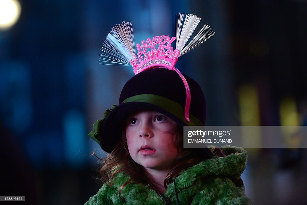A young girl watches during New Year's celebrations on Times Square on December 31, 2012 in New York. A million people cheered in New York's Times Square as the traditional crystal ball dropped to mark the start of 2013, bringing a rolling global New Year's party that kicked off in Australia to US shores. AFP PHOTO/EMMANUEL DUNAND