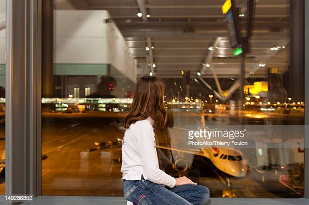 Young girl watches from airport terminal window as flight crew prepare commercial airplane for boarding