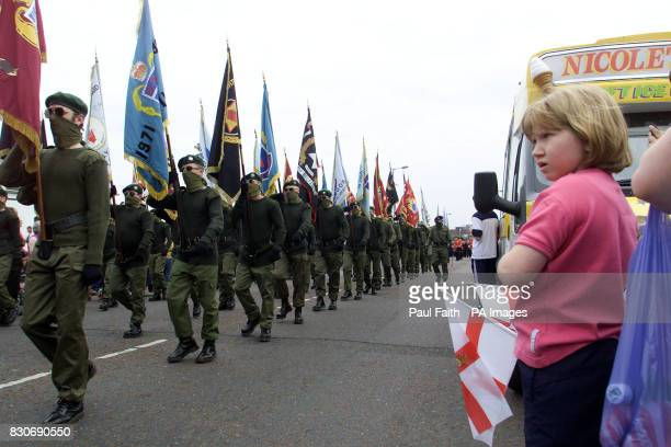 A young girl watches masked UFF men marching on the Shankill Road to pay their respect to Jackie Coulter of the UFF Mr Coulter was shot dead last...