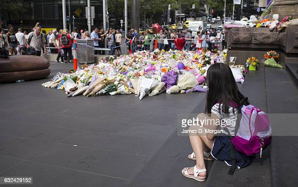 A young girl watches the flowers and messages of condolence lie on Bourke Street Mall on January 23 2017 in Melbourne Australia Five people including...
